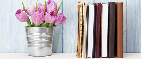 Fresh pink tulip flowers bouquet and books on shelf in front of stone wall