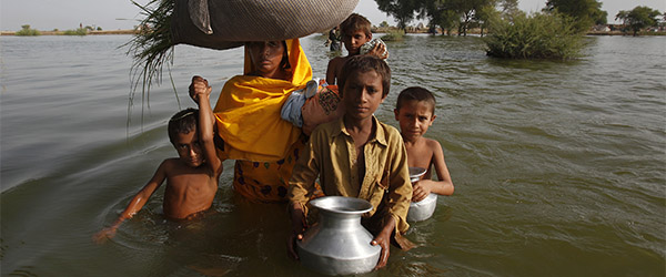 A family displaced by flooding wades through floodwaters is pictured as they return to their village of Bello Patan, in Pakistan's Sindh province in this September 21, 2010 file photo. A new plan to curb global warming risks becoming a battleground between rich and poor nations and could struggle to get off the ground as negotiators battle over the fate of the ailing Kyoto climate pact. To match Analysis CLIMATE-DEAL/ REUTERS/Akhtar Soomro/Files (PAKISTAN - Tags: ENVIRONMENT POLITICS)